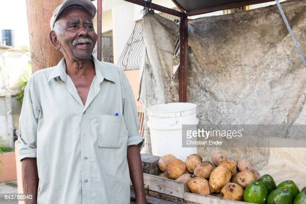 Santa Domingo Dominican republic November 30 2012 A elderly man is laughing while standing in front of a market trolley selling vegetables
