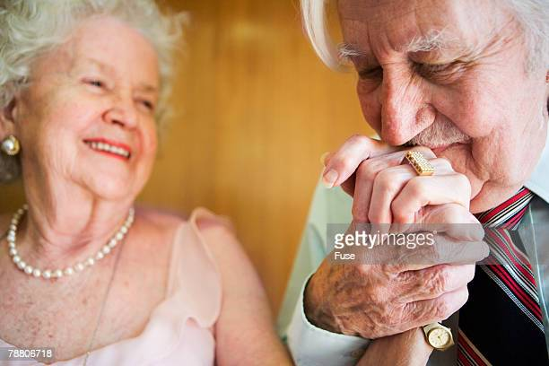 Elderly Man Kissing Wife's Hand