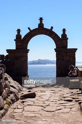 Elderly man knitting next to a stone archway : Stock Photo