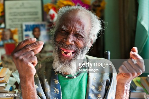 Elderly man laughing and snapping his fingers.
