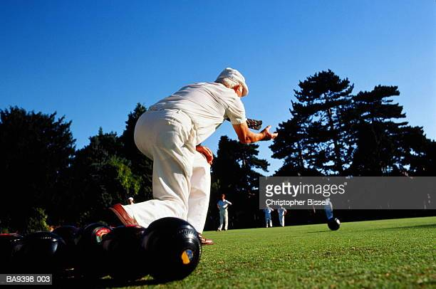 Elderly man lawn bowling, low  angle, rear view