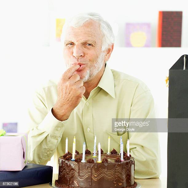 Elderly man licking icing from a cake with his finger