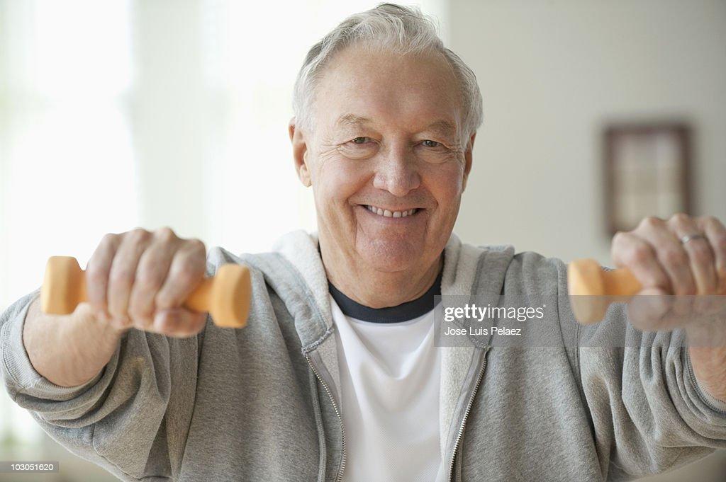 Elderly man lifting weights : Stock Photo