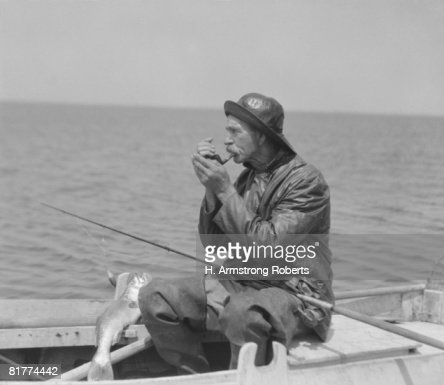 Elderly man lighting pipe, sitting in row boat, wearing foul weather gear. : Stock Photo