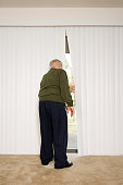 Elderly man looking out of blinds