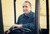Positive glad elderly man of winery goes on loader