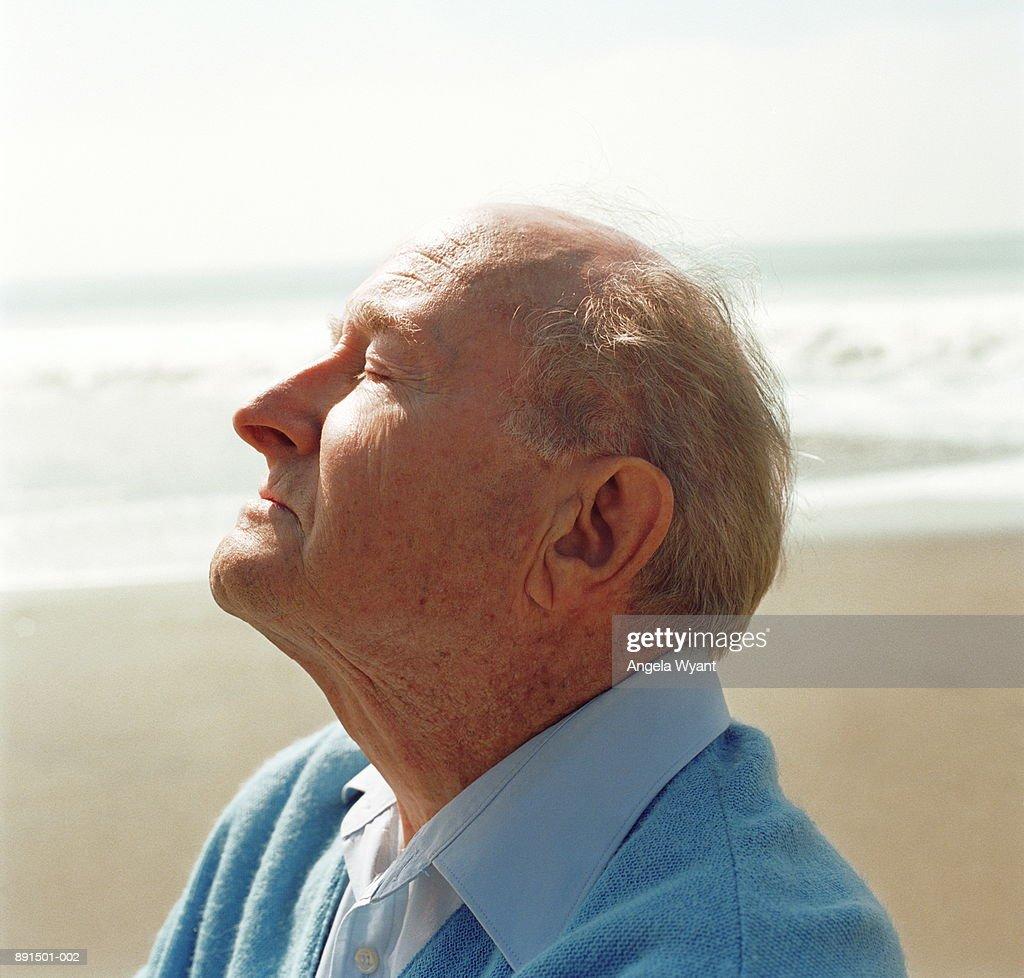 Elderly man on beach, head raised towards sun : Stock Photo