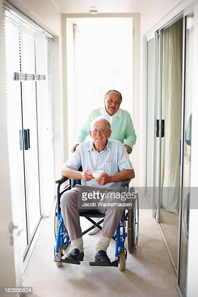 Älterer Mann auf dem Rollstuhl unterstützt durch seine Frau