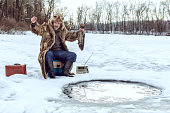 Elderly man on winter fishing rejoices caught fish.