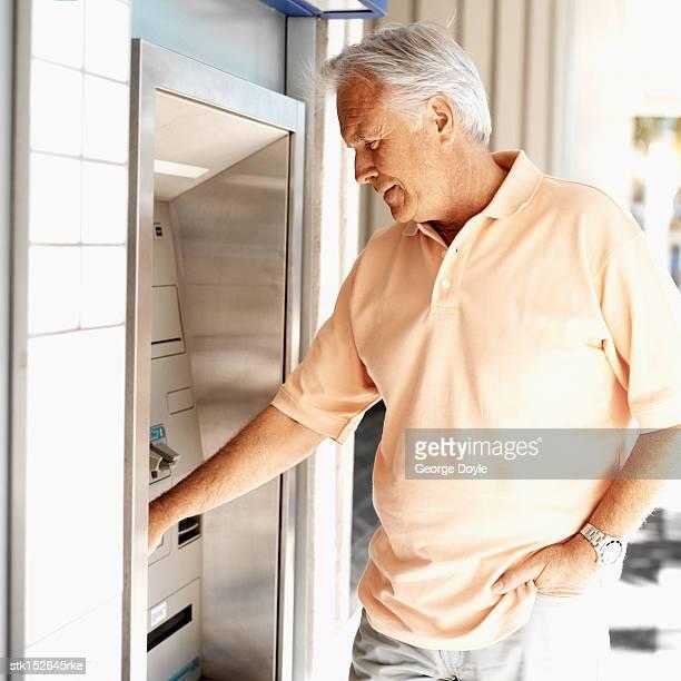 Elderly man operating an automatic cash machine