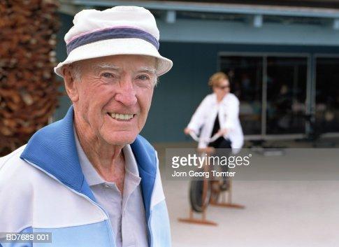 Elderly man, portrait, woman on exercise bike in background : Stock Photo