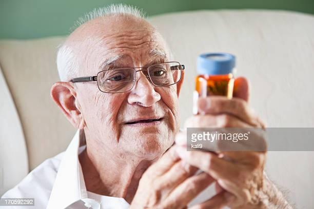 リーティング医学ボトルを見る老人男性