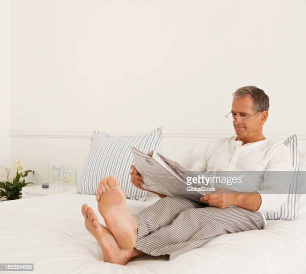 Elderly man reading newspaper in bed