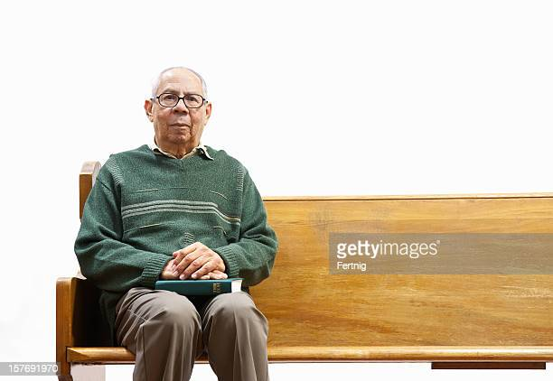 Elderly man sitting alone on a church pew