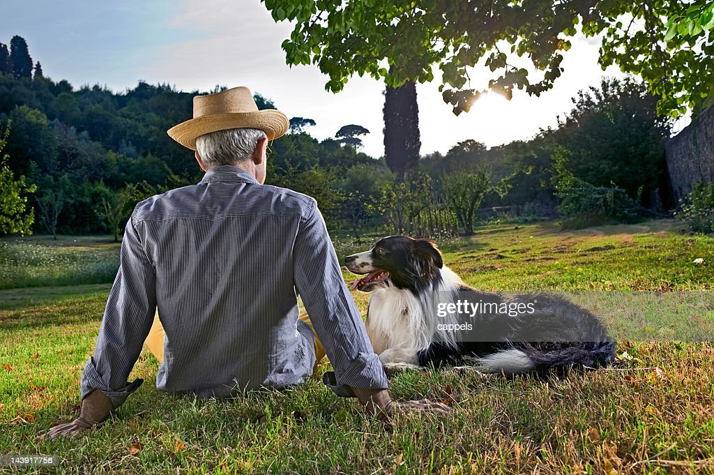Elderly Man Sitting In Sunset With His Dog.Color Image : Stock Photo