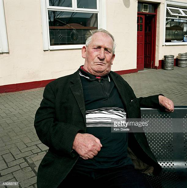 Elderly man sitting on bench in sun, Ireland