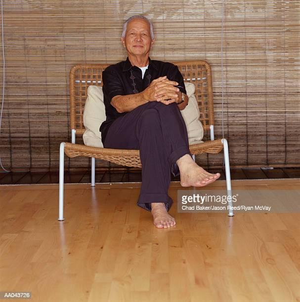 Elderly man sitting with legs crossed, portrait