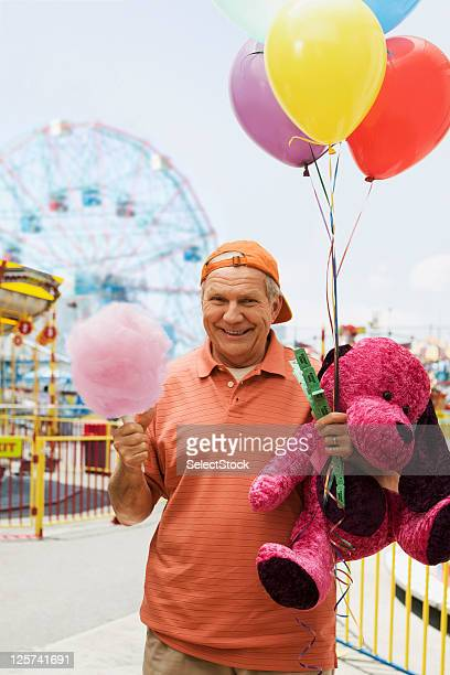 Elderly man smiling and holding cotton candy, baloons and teddy bear