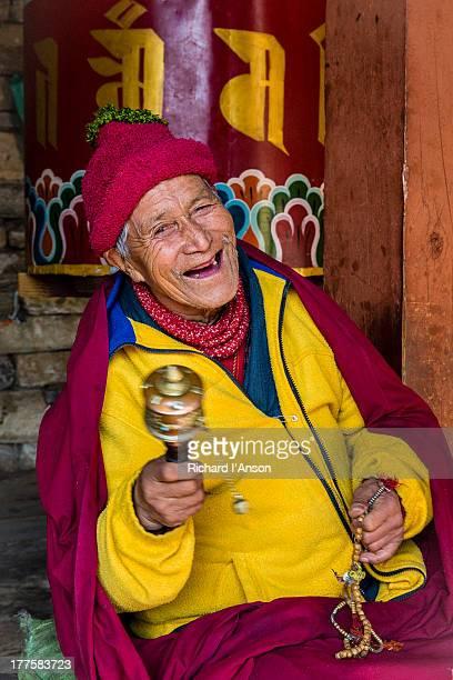 Elderly man spinning prayer wheel