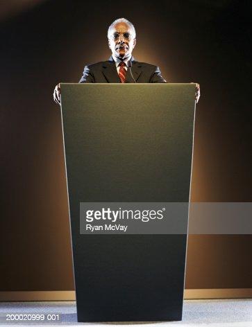 Elderly man standing at podium : Stock Photo