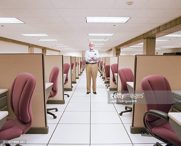 Elderly man standing in hallway between rows of empty cubicles