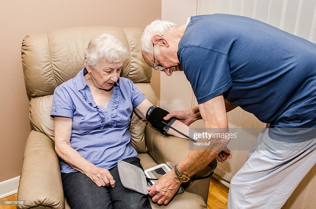 Elderly man taking blood pressure of his wife