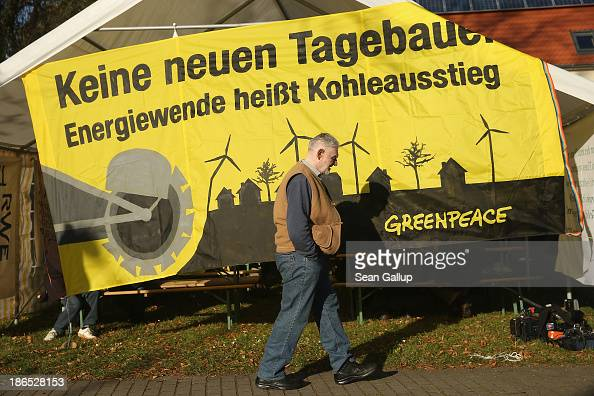 A elderly man walks past a Greenpeace banner that reads 'No new openpit mines Energy transition means abandoning coal' at a protest against the...