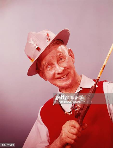 Elderly man wear fishing hat, holding rod & reel smiling. (Photo by H. Armstrong Roberts/Retrofile/Getty Images)