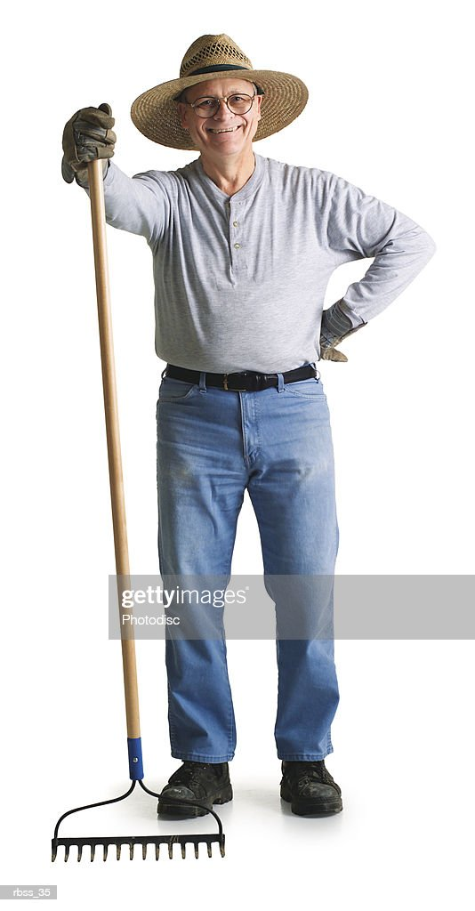 Elderly man wearing a straw hat and holding a rake smiles at the camera. : Stock Photo