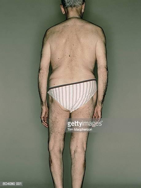 Elderly man wearing striped pants, rear view (cross-processed)