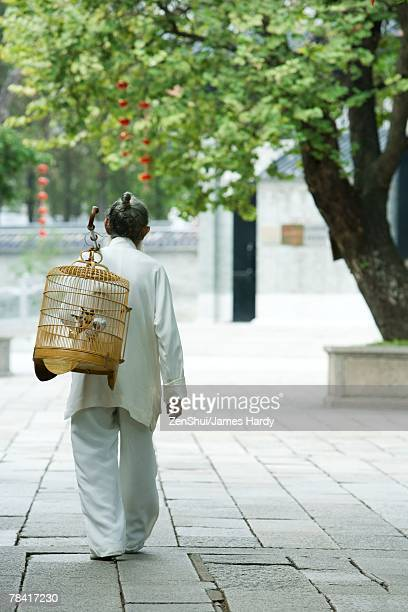 Elderly man wearing traditional Chinese clothing carrying bird cage over shoulder, rear view