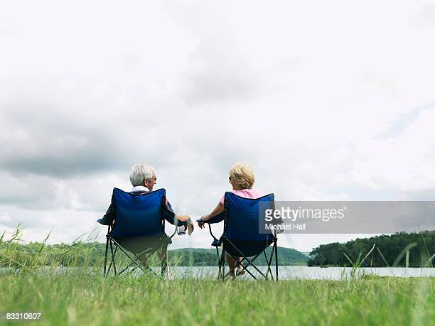 Elderly Man & Woman relaxing in deck chairs