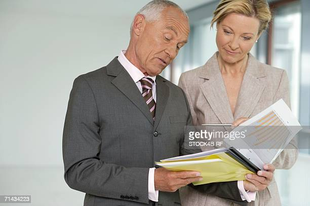 Elderly manager with blond business woman studying business papers