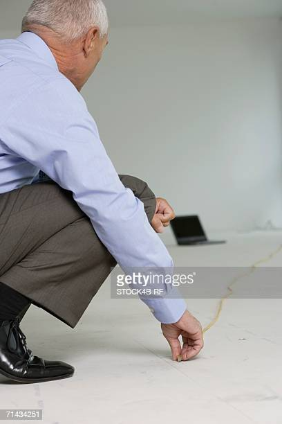 Elderly manager with folding rule squatting on the floor, laptop on floor in the background