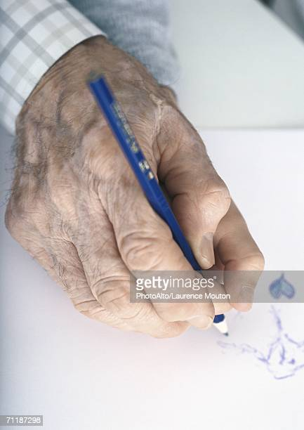 Elderly man's hand drawing with colored pencil