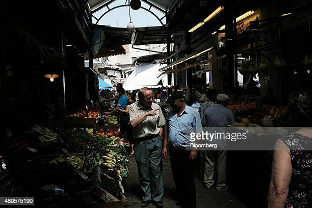 Elderly men pause beside grocery stalls to talk while visiting Kapani market in Thessaloniki Greece on Monday July 13 2015 Greece has been in...