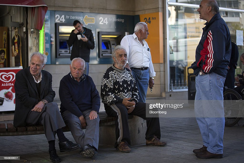 Elderly men sit and chat in front of a Bank of Cyprus Plc branch in Nicosia, Cyprus, on Friday, March 29, 2013. Cypriots face a second day of bank controls over their use of the euro as officials in Europe urged the country to move quickly to lift the restrictions, the first time they have been imposed on the common currency. Photographer: Simon Dawson/Bloomberg via Getty Images