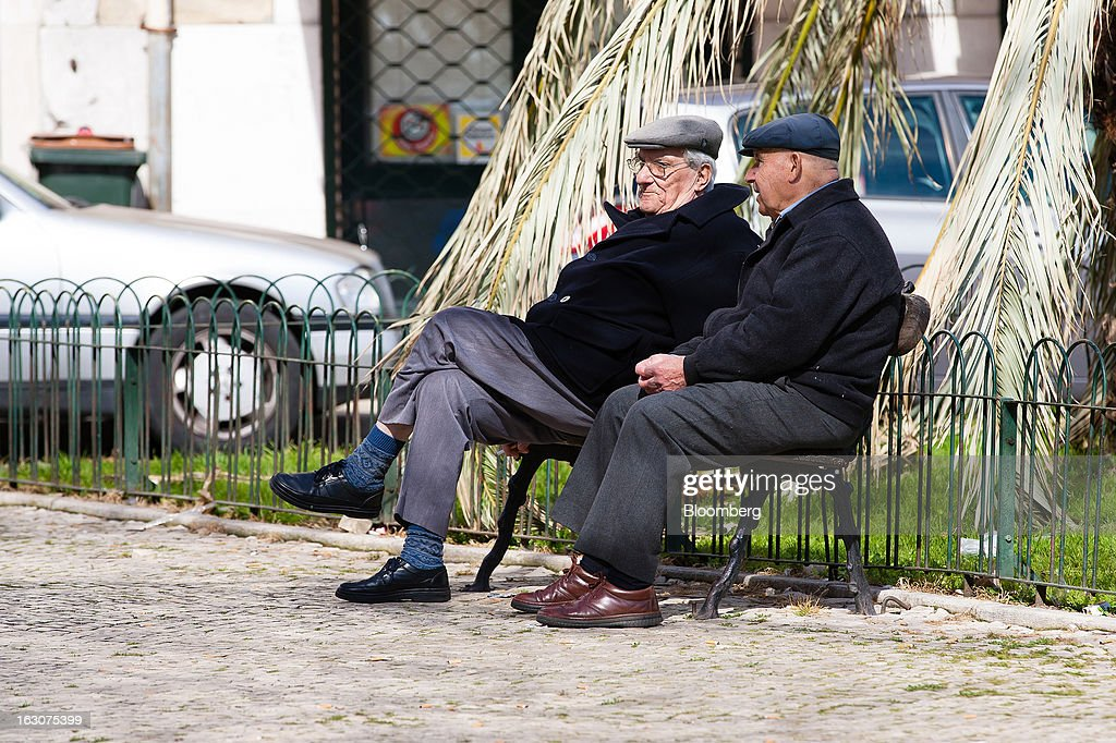 Elderly men sit and talk on a street bench in the Alfama old quarter of Lisbon, Portugal, on Saturday, March 2, 2013. Prime Minister Pedro Passos Coelho is battling rising joblessness and lower demand from European trading partners as he raises taxes to meet the terms of a 78 billion-euro ($104 billion) aid plan from the European Union and the International Monetary Fund. Photographer: Mario Proenca/Bloomberg via Getty Images