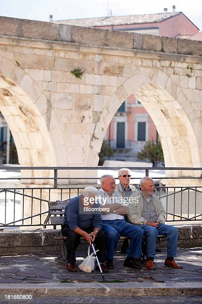 Elderly men sit on a bench near an outdoor market at Piazza Garibaldi in Sulmona Italy on Saturday Sept 21 2013 Between 2000 and 2010 the percentage...
