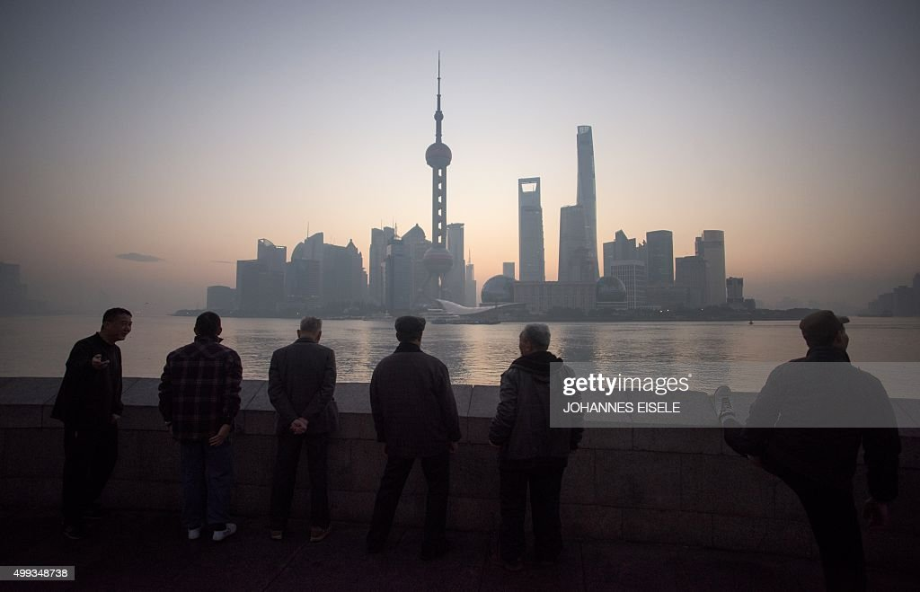 Elderly men stand together in front of the skyline of the Lujiazui Financial District in Pudong in Shanghai at dawn on December 1 2015 AFP PHOTO /...