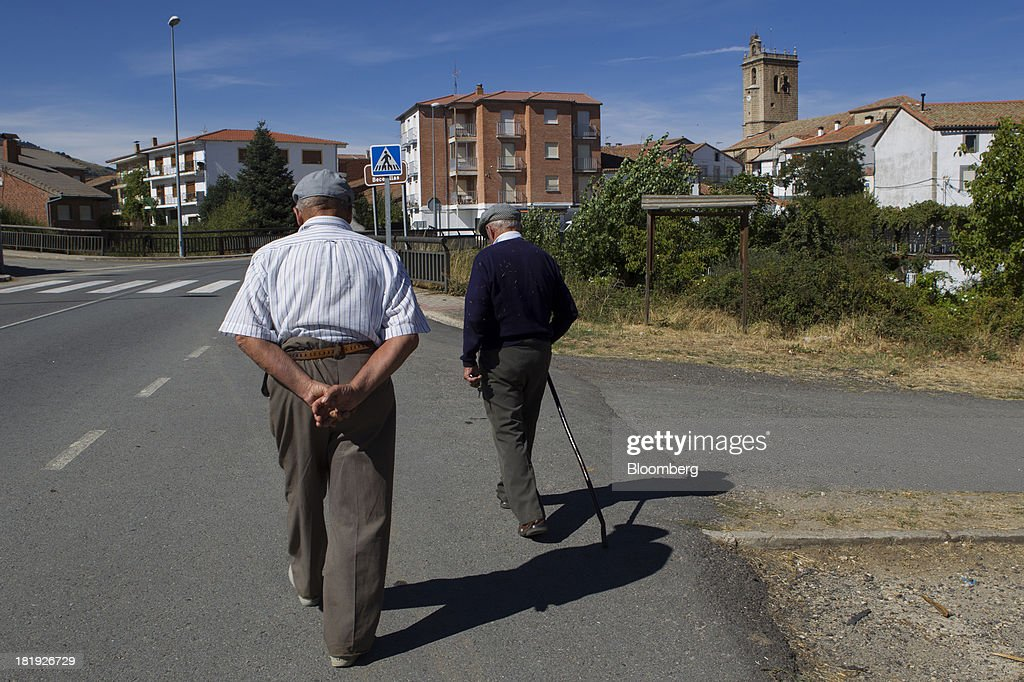Elderly men stroll along the tarmac of an empty main road in Becedas, Spain, on Thursday, Sept. 26, 2013. Prime Minister Mariano Rajoy is increasingly dependent on the pension reserve fund as it reaps lower returns on Spanish sovereign debt, which comprise 97.5 percent of its investments. Photographer: Antonio Heredia/Bloomberg via Getty Images