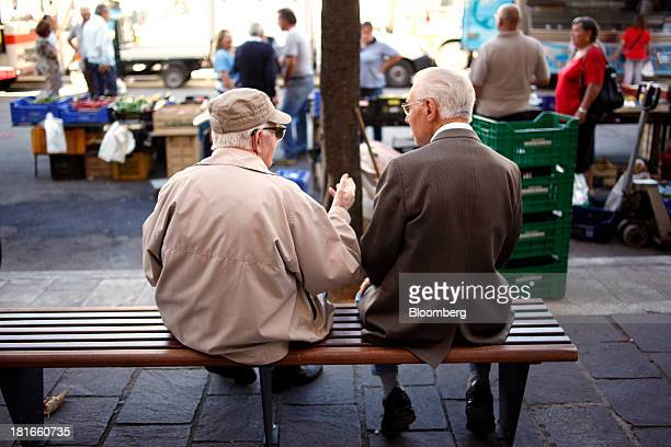 Elderly men talk as they sit on a bench near an outdoor market at Piazza Garibaldi in Sulmona Italy on Saturday Sept 21 2013 Between 2000 and 2010...