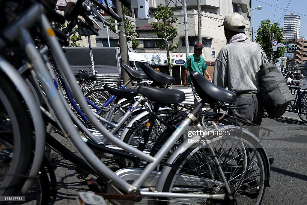 Elderly men walk past bicycles parked outside a store, unseen, in Tokyo, Japan, on Monday, July 8, 2013. The number of Japanese seniors living alone will rise 54 percent to 7.17 million in 2030 from 4.66 million in 2010, according to the National Institute of Population and Social Security Research, set up by the Ministry of Health, Labour and Welfare. To manage the costs stemming from the aging society, the government aims to push back the pension age to 65 from 60 in stages through 2025. Photographer: Kiyoshi Ota/Bloomberg via Getty Images