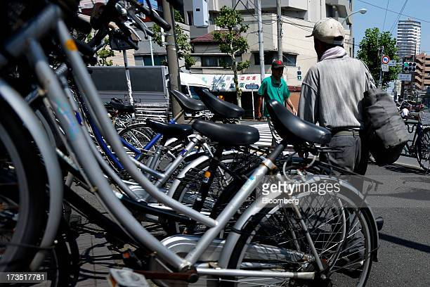 Elderly men walk past bicycles parked outside a store unseen in Tokyo Japan on Monday July 8 2013 The number of Japanese seniors living alone will...