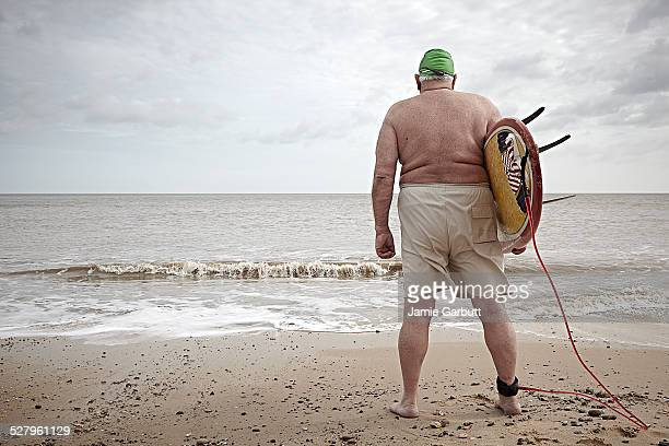 Elderly overweight surfer with back to camera