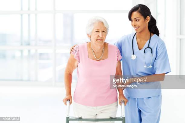Elderly Patient Being Assisted By Nurse In Using Walker