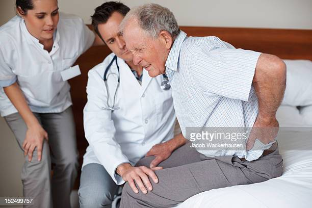 Personnes âgées patient étant aidé par deux docteurs