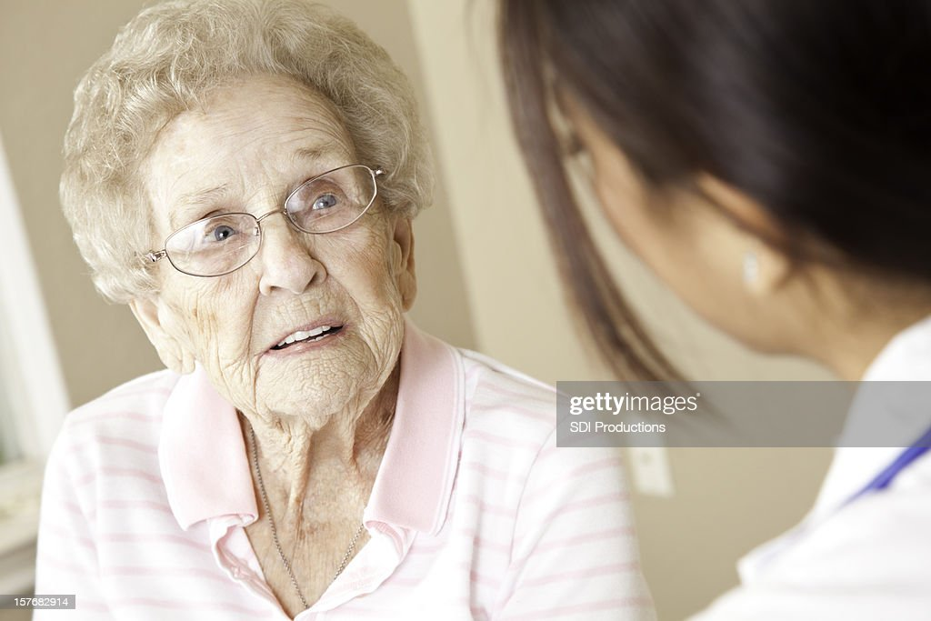 Elderly Patient Receiving Advice From Female Doctor : Stock Photo