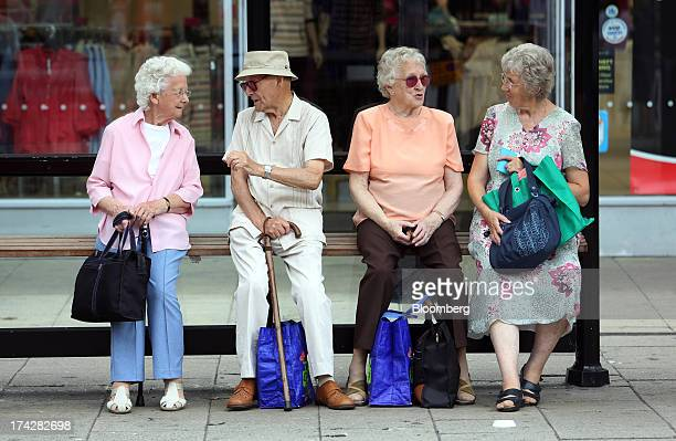 Elderly people sit with their shopping bags as they wait for transportation at a bus stop in Hastings UK on Tuesday July 23 2013 UK retail sales rose...