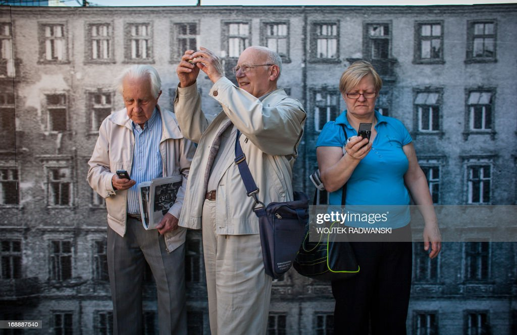 Elderly people take pictures during the opening ceremony of the installation of the 1-10 scale model of the largest synagogue in pre-war Warsaw, the Great Synagogue on May 16, 2013 in Warsaw. The model is installed on the place near the original location 70 years after it was destroyed during World War II Warsaw Ghetto liquidation.